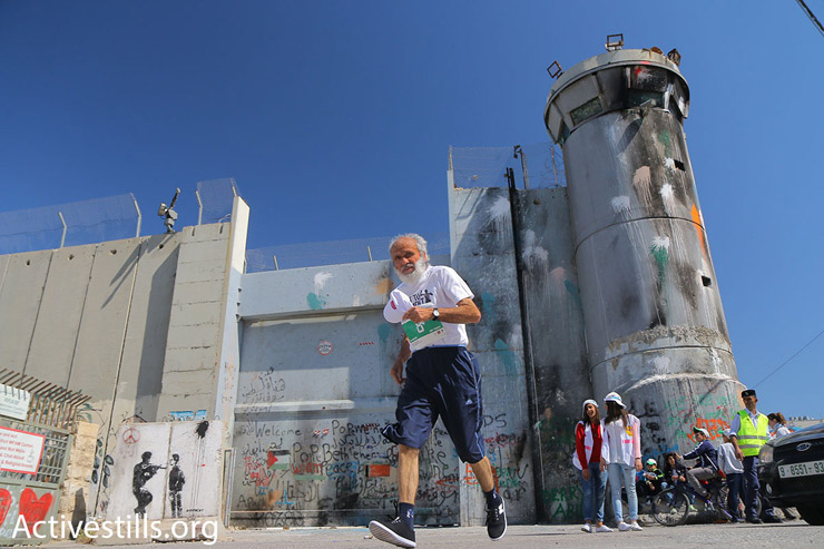 A participant in the 2016 Palestine Marathon runs in front of an Israeli military watchtower and the concrete separation barrier, Bethlehem, West Bank, April 1, 2016. (Ahmad al-Bazz/Activestills.org)