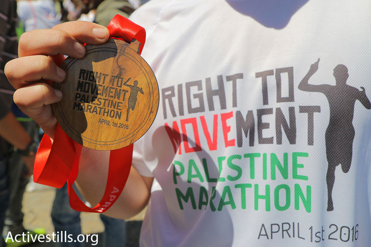 A participant in the 2016 Palestine Marathon displays the carved olive wood medallion given to runners who finish the competition, Bethlehem, West Bank, April 1, 2016. (Ahmad al-Bazz/Activestills.org)