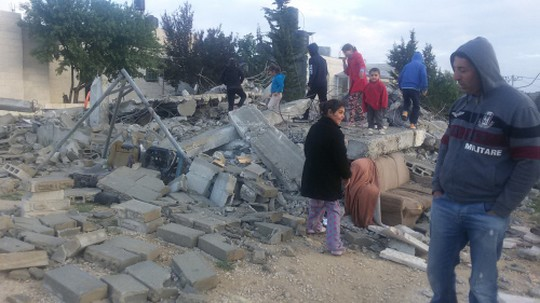 Residents of al-Walaje survey the destruction following the demolition of three homes in the village overnight on Tuesday, April 12, 2016.
