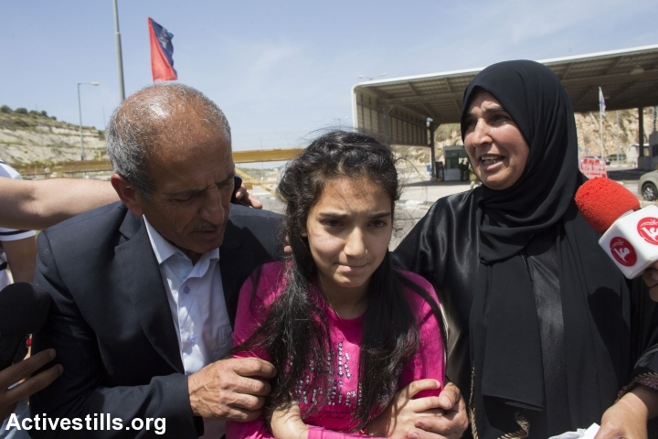 Journalists talk to 12-year-old Dima al-Wawi and her parents at the Jabara checkpoint, where Israeli authorities released her after 75 days imprisonment, West Bank, April 24, 2016. (Oren Ziv/Activestills.org)