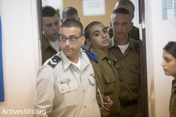 Israeli soldier Elor Azaria (center), who has been charged with manslaughter for shooting an incapacitated Palestinian stabbing suspect in Hebron, is escorted into military court, March 29, 2016. (Oren Ziv/Activestills.org)