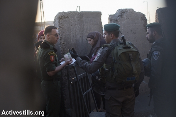 A Palestinian Authority police officer speaks to an Israeli Border Police officer at the Qalandiya checkpoint separating Jerusalem and Ramallah, July 10, 2015. (Oren Ziv/Activestills.org)