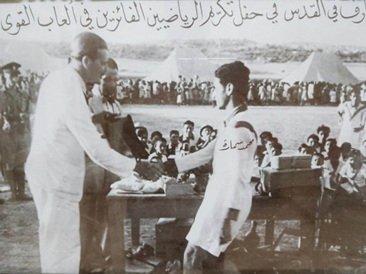 My grandfather, Mohammed Samara, shaking hands with an official at a football tournament in Jerusalem during the British mandate of Palestine, 1946. Photo courtesy of the Samara family.