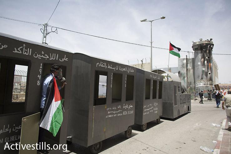 The 'Return Train' reaches the Israel wall separating Bethlehem from Jerusalem, May 15, 2016. (Oren Ziv/Activestills.org)