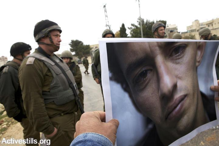 A protester holds a photo of Omar Alaaeddin, a 25-year-old who in 2010 was alleged tortured by Israeli security forces, March 26, 2010. (Anne Paq/Activestills.org)