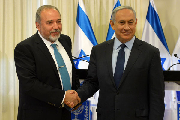 Prime Minister Benjamin Netanyahu and newly appointed defense minister Avigdor Liberman sign new coalition agreement, May 25, 2016. (Amos Ben Gershom/GPO)