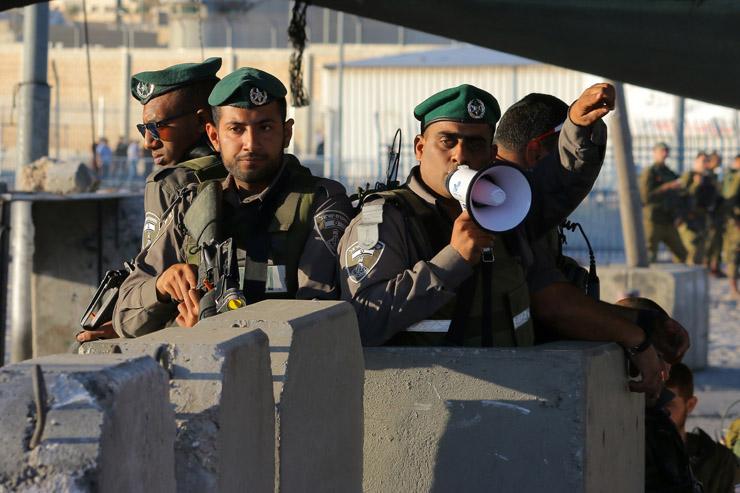 Israeli Border Police direct Palestinian worshipers through the Qalandiya checkpoint separating Ramallah and Jerusalem on their way to pray at Al-Aqsa Mosque for the second Friday of Ramadan, June 17, 2016. (Ahmad Al-Bazz/Activestills.org)