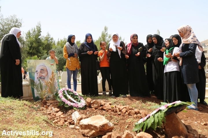Palestinians take part in the funeral of Jamal Dwekat, 20, in Balata village, near Nablus, West Bank, June 8, 2016. Behind Dwekat's grave is a photo of Hamas founder Sheikh Ahmad Yassin, who was assassinated by the Israeli army in 2004. (photo: Ahmad al-Bazz)