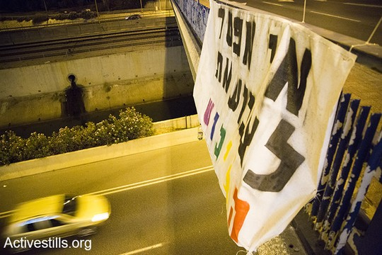 Israeli activists hang banners with anti-occupation slogas across bridges at the entrances to Tel Aviv, anti-occupation slogans across Tel Aviv in the run-up to the 2016 pride parade. (photo: Activestills.org)