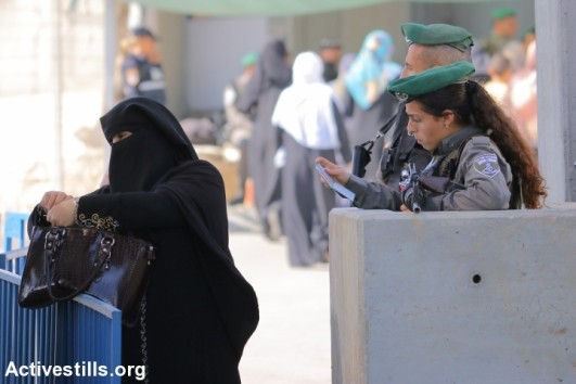 Palestinian women cross Qalandiya checkpoint, a main crossing point between Jerusalem and the West Bank city of Ramallah. (Ahmad al-Bazz/Activestills.org)