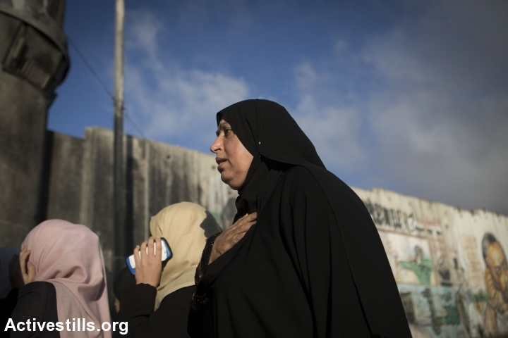 Palestinian women cross Qalandiya checkpoint, a main crossing point between Jerusalem and the West Bank city of Ramallah, as they head to Al-Aqsa Mosque for the first Friday prayer of the holy Muslim month of Ramadan. (photo: Ahmad al-Bazz/Activestills.org)