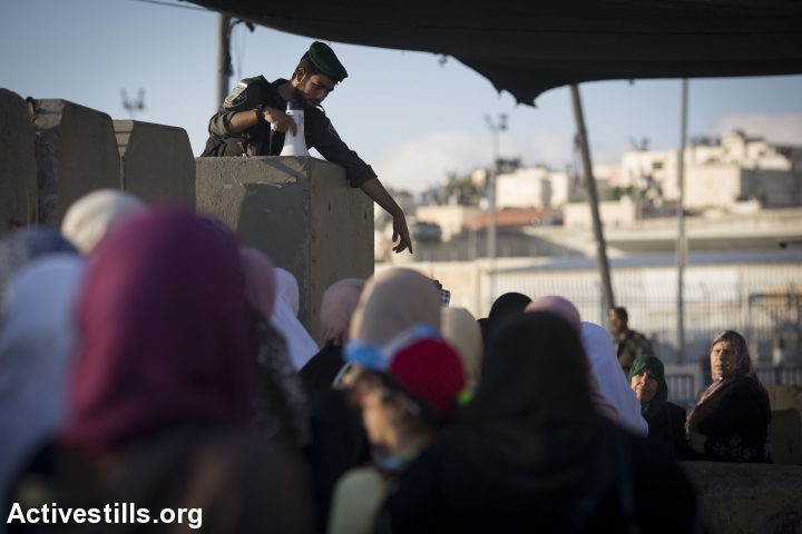 An Israeli Border Policemen directs Palestinian woman through Qalandiya checkpoint as they head to Al-Aqsa Mosque in Jerusalem for the first Friday prayers of Ramadan. (photo: Oren Ziv/Activestills.org)