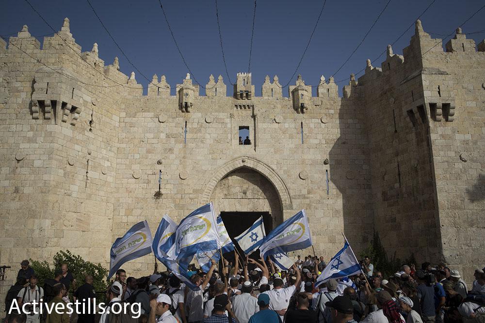 Nationalist Jewish Israelis, largely bussed-in yeshiva students, enter the Muslim Quarter of Jerusalem's Old City through Damascus Gate on Jerusalem Day, June 5, 2016. (Oren Ziv/Activestills.org)