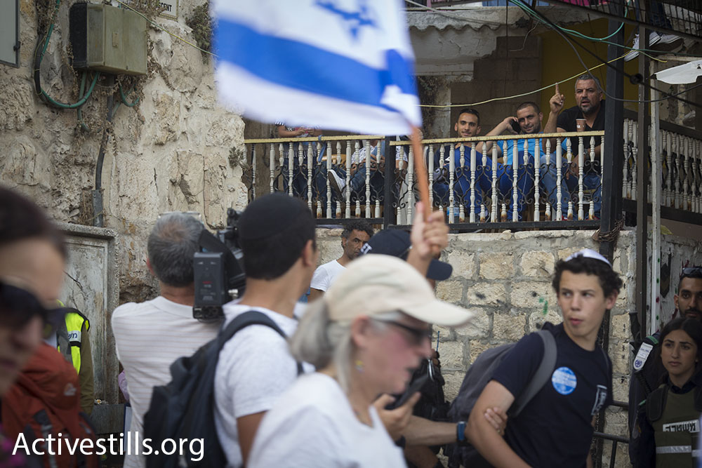 Palestinian men watch the march go by from inside a private home in the Muslim Quarter of Jerusalem's Old City, June 5, 2016. The High Court has ordered police to reign in right-wing verbal and physical violence during the march in recent years. (Oren Ziv/Activestills.org)