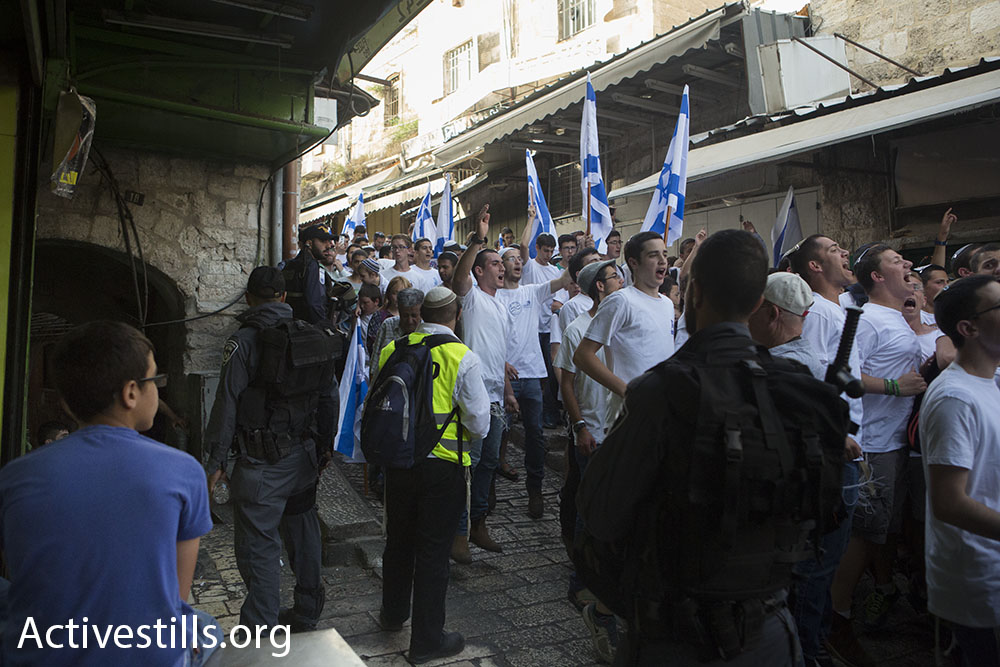 Nationalist Jewish Israelis march through the alleyways of the Muslim Quarter of the Old City during the 'March of the Flags' on Jerusalem Day, June 5, 2016. (Oren Ziv/Activestills.org)