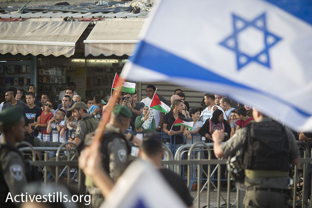 Behind police barricades, Palestinian residents of Jerusalem hold a counter-protest against the nationalist display in their neighborhood, June 5, 2016. In years past physical and verbal violence against Palestinians was a central feature of the march. (Oren Ziv/Activestills.org)
