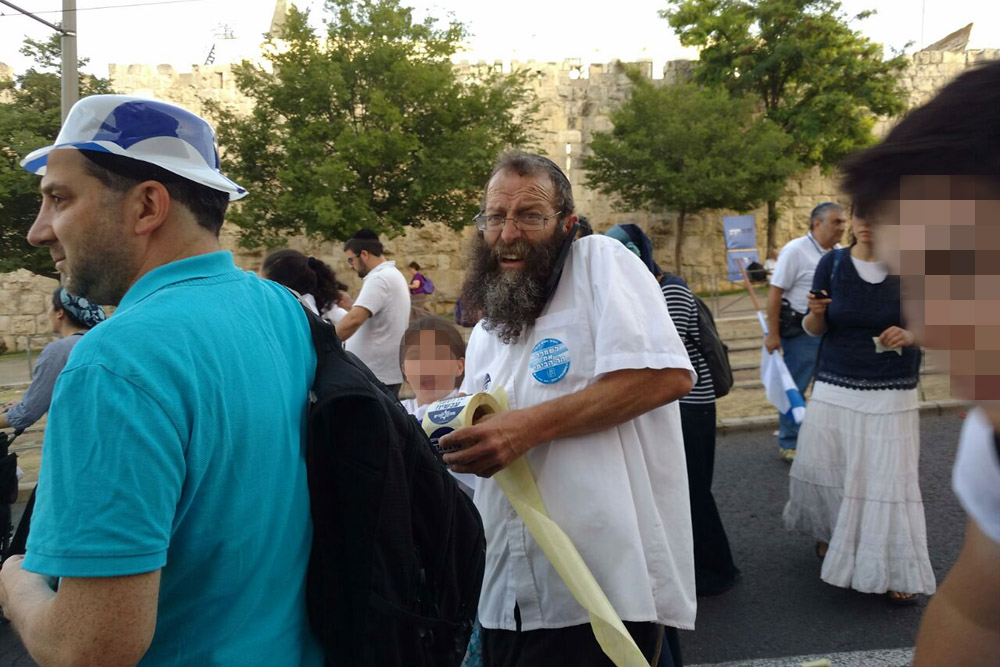 Radical right-wing Israeli activist Baruch Marzel hands out stickers advocating population transfer of Palestinians, East Jerusalem, June 5, 2015. The stickers read: 'There's no coexistence with them; Transfer now'. (Orly Noy/+972 Magazine)