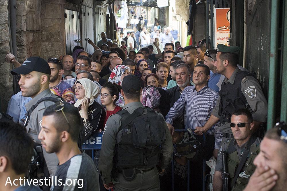 Israeli police keep Palestinian residents of the Old City's Muslim Quarter away from nationalist Jewish Israelis marching through their neighborhood, Jerusalem Day, June 5, 2016. (Oren Ziv/Activestills.org)