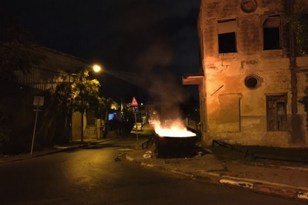 A trash container is set ablaze in the middle of a Jaffa street. (photo: Yael Marom)