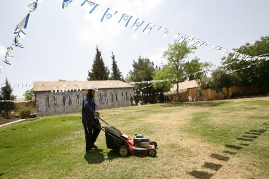 An Israeli settler mows the lawn in the settlement of Susya in the south Hebron Hills, May 25, 2009. (photo: Miriam Alster/Flash90)