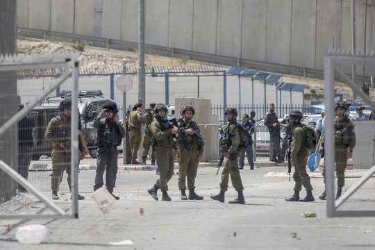Israel soldiers and police officers at the Qalandiya checkpoint shortly after the two siblings were shot, April 27, 2016. (Yonatan Sindel/Flash90)