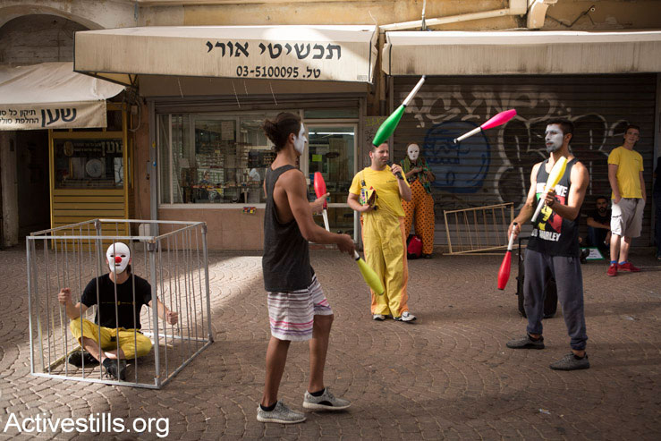 Israeli and Palestinian circus artists protest in Tel Aviv for the release of Palestinian clown, Mohammed Abu Sakha, who is being imprisoned by Israel, July 5, 2016. (Oren Ziv/Activestills.org)
