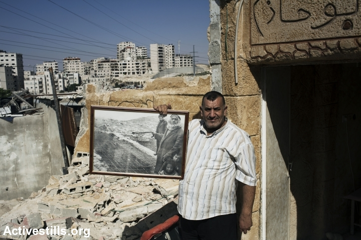 A Palestinian father stands in the ruins of his son's family home a few hours after it was demolished by Israeli authorities, East Jerusalem, May 20, 2013. He is holding a portrait from 1983 in which he and his own father are seen standing near their demolished home in the Anata neighborhood. Seven family members, including 5 children were displaced due to the demolition. (photo: Activestills.org)