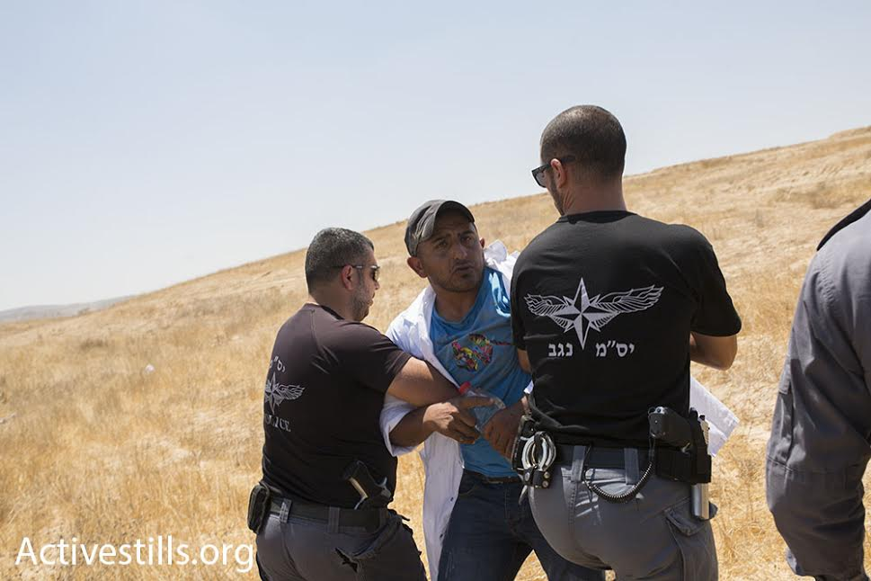 Israeli police detain an activist during a march in the unrecognized Bedouin village of Al-Araqib, Negev Desert, July 24, 2016. (photo: Oren Ziv/Activestills.org)