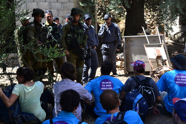 Activists with the Center for Jewish Non-Violence lock arms and sit on the ground as police order them to leave, Hebron, July 15, 2016. (Dahlia Scheindlin) Police detained six Israeli activists for seven hours.
