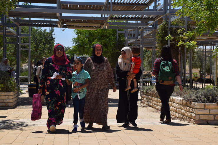 Palestinian women from Susya walk into the archeological park with their children, many of whom had never seen the caves in which the older generation was born and raised, Susya, South Hebron Hills, July 14, 2016. (Michael Schaeffer Omer-Man)