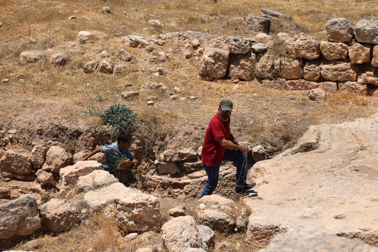 A Palestinian man and his son exit a cave in the former site of the village of Susya. Many younger residents had never seen the place where there parents were born and raised, Susya, South Hebron Hills, July 14, 2016. The stories were translated from Arabic into Hebrew and English. (Michael Schaeffer Omer-Man)