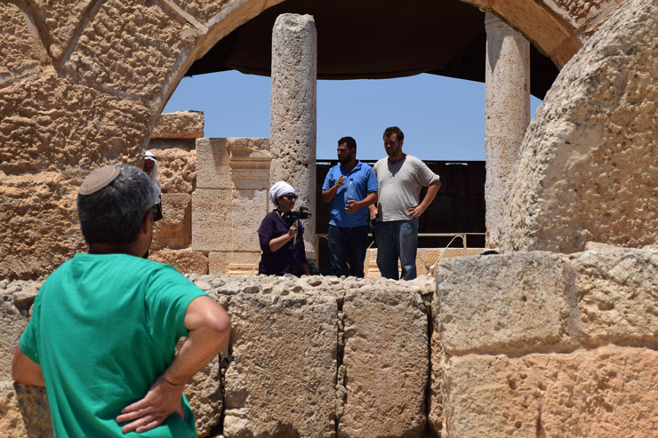 An employee of the JNF-supported archeological park watches and listens as Susya resident Nasser Nawaj'ah and Center for Jewish Non-Violence activist Isaac Kates Rose address the group, Susya, South Hebron Hills, July 14, 2016. (Michael Schaeffer Omer-Man)