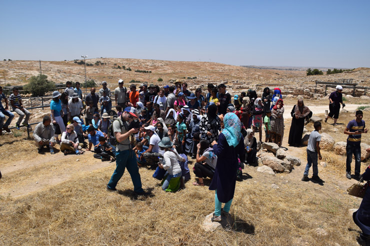 The group of roughly 80 Palestinians from Susya and 40 North American and European activists with the Center for Jewish Non-Violence pose for a photo before leaving the former site of the village of Susya, South Hebron Hills, July 14, 2016. The stories were translated from Arabic into Hebrew and English. (Michael Schaeffer Omer-Man)