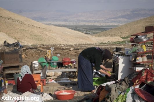 A Palestinian woman from the small Jordan Valley community of Ein Kruzliya prepares bread among her belongings after an Israeli military demolition a few days earlier, Jordan Valley, West Bank, February 10, 2016. (Oren Ziv/Activestills.org)