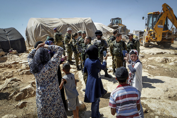 Palestinians look on as Israeli soldiers and Civil Administration contractors demolish their homes and other structures in a small village in the South Hebron Hills, West Bank, June 19, 2016. (Wisam Hashlamoun/Flash90)