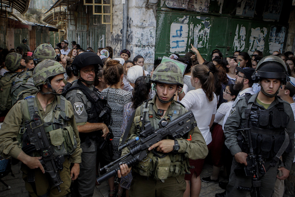 Israeli soldiers escort Jewish settlers as they tour the Old City of the occupied West Bank city of Hebron, June 4, 2016. The Israel army has enforced segregation in the city for over two decades, restricting residents' movement according to their religion. (Wisam Hashlamoun/FLASH90)