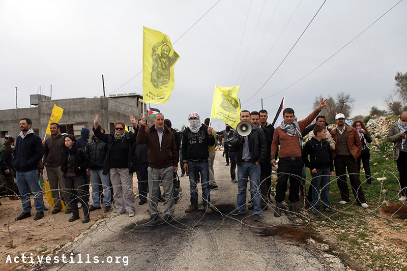 Protesters stand behind the barbed wire put across the road by Israeli soldiers during the weekly demonstration in Kafr Qaddum, West Bank, December 30, 2011.