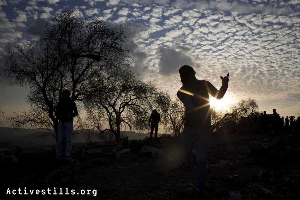 Palestnians youth throw stones at Israeli soldiers, during clashes following the funeral march of Said Jasir, 85 years old, in the West Bank village of Kfar Qaddum, January 2, 2014.