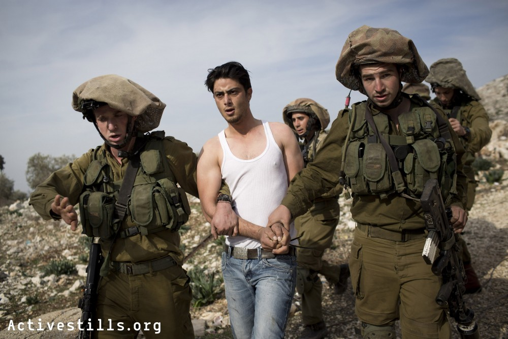 Israeli soldiers arrest a 24 years old Palestinian youth during the weekly protest against the occupation in the West Bank village of Kafr Qaddum, January 3, 2014.