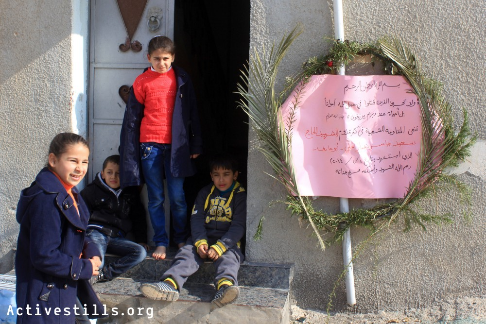 Palestinian children sit in front of Said Jaser's house in the West Bank village of Kafr Qaddum, January 4, 2014.