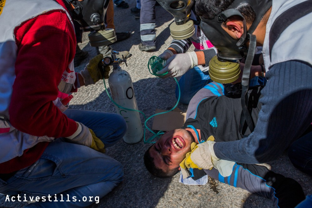 A man receives medical treatment after inhaling large amounts of tear gas shot at him by Israeli solders during the weekly demonstration in Kafr Qaddum, a West bank village located east of Qalqiliya, January 24, 2014.
