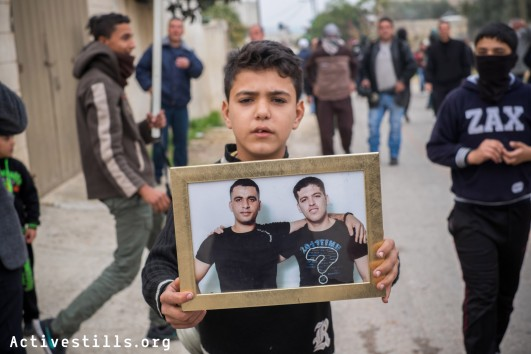 A Palestinian boy holds a picture showing prisoners from his village during the weekly protest in Kafr Qaddum, a West Bank village located east of Qalqiliya, December 19, 2014.