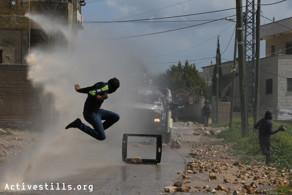 Palestinian youth jumps as a water canon sprays water during clashes with the Israeli army at the weekly protest against the occupation, Kafr Qaddum, West Bank, March 13, 2015.