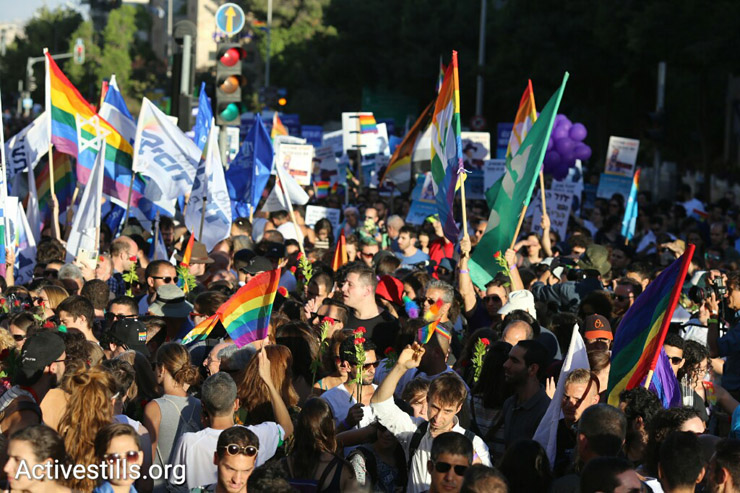 Thousands of Israelis turn out for the Jerusalem Pride Parade, many holding flowers to lay at a memorial for 16-year-old Shira Banki, who was stabbed to death in a hate crime at the 2015 parade, July 21, 2016. (Oren Ziv/Activestills.org)