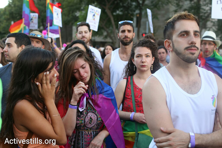 Participants at the Jerusalem Pride Parade console each other at a monument to Shira Banki, a 16-year-old who was murdered in a hate crime at the event a year earlier, West Jerusalem, July 21, 2016. (Oren Ziv/Activestills.org)