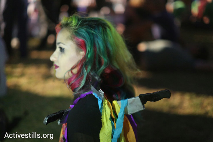 A participant at the Jerusalem Pride Parade wears a costume referring to the hate crime that took the life of Shira Banki, a 16-year-old who was murdered at 2015's Pride Parade, West Jerusalem, July 21, 2016. (Oren Ziv/Activestills.org)