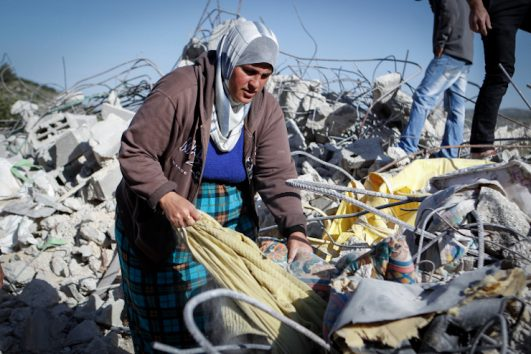 A Palestinian woman sorts through the rubble of her demolished home in the West Bank village of Surif, April 4, 2016. The Israeli army demolished the home because it says it was unauthorized. (Wisam Hashlamoun/FLASH90)
