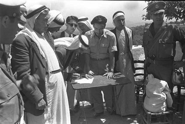 The heads of the Arab city Umm al-Fahm, in the presence of Israeli military officials, sign an oath of allegiance to the State of Israel after the city came under Israeli control in the 1948 war.