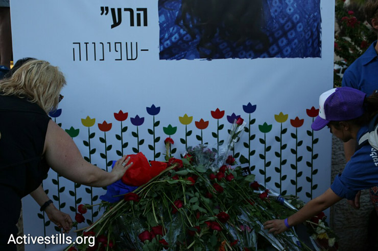 Participants of the Jerusalem Pride Parade lay flowers at the foot of a giant photo of Shira Banki, who was murdered in a hate crime at the 2015 parade, West Jerusalem, July 21, 2016. (Oren Ziv/Activestills.org)