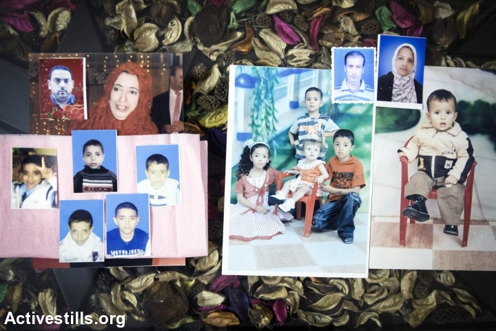 Photos of 14 killed members of the Abu Amer family are displayed in Bani Suheila, east of Khan Younis, November 15, 2014. A total of 16 members of the Abu Amer family were killed on July 29, 2014 in an airstrike that targeted the al-Dali building in Khan Younis. In total, 34 people from five families were killed in the attack. It was the deadliest attack on a residential building in the 2014 Israeli military offensive. (Anne Paq/Activestills.org)